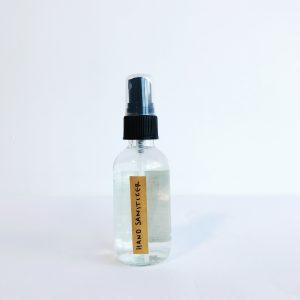 2oz clear bottle with black plastic fine mist sprayer filled with Oneka Elements lemon hand sanitizer